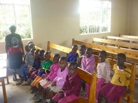 Die Kinder sitzen auf geliehenen Kirchenbänken. Eigene Möbel gibt es nicht.